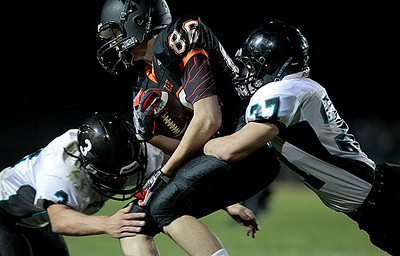 Kyle Grillot - kgrillot@shawmedia.com   McHenry junior Mike Borst (86) is tackled by Woodstock North junior Jeremy Haymond (37) and junior Jimmy Krenger (3) during the fourth quarter of the football game at McCracken field Friday, September 13, 2013. McHenry beat Woodstock North 35 - 28.