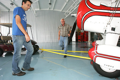 H. Rick Bamman -hbamman@shawmedia.com   Galt Airport manager Justin Cleland (left) and owner Claude Sonday work to park a 1942 Boeing Stearman in one of the hangers.