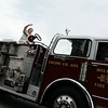 Jeff Krage – For Shaw Media<br /> A woman waves from atop a fire engine during Friday's Emergency Vehicle Lights and Sirens Parade as it heads north on Route 31 in North Aurora.<br /> North Aurora 8/1/14