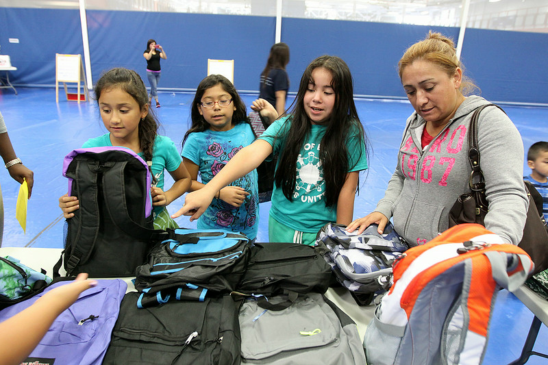 Jeff Krage – For Shaw Media<br /> Josefa Cruz, right, of Elgin helps her daughter's Sherlin, second from left, and Noemy, second from right, both 11, and family friend Heidi Alvarez, left, 9, also from Elgin, select a backpack during Saturday's Project Backpack inside the Spartan Events Center at Elgin Community College.<br /> Elgin 8/9/14