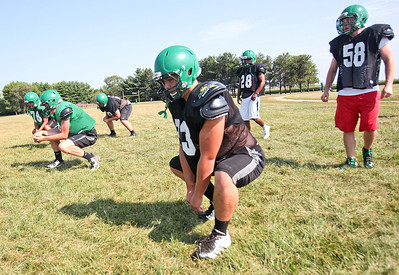 """Michelle LaVigne - For Shaw Media While Alden-Hebron High School seniors Joshua Johnson (center back,) and Trevor Redlin wait their turn, junior Taylor Glenn (closest,) heads down the field while executing a """"duck walk"""" during warm-ups at football practice in Hebron on August 14, 2015."""