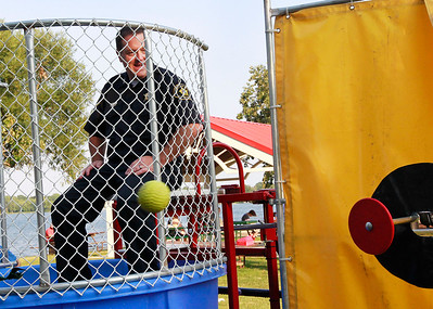 Candace H. Johnson Deputy Chief Mike Scott with the Round Lake Beach Police Dept. watches the ball as he sits in the dunk tank during National Night Out at Lakefront Park in Round Lake Beach.