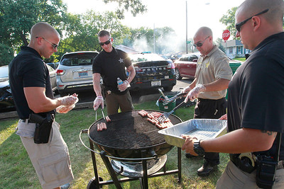 Candace H. Johnson Heath Atwell, Tim Schuster, Rich Chiarello, and Tim Gannon, all with the Round Lake Beach police dept., grill hot dogs for everyone during National Night Out at Lakefront Park in Round Lake Beach.