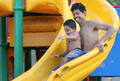 Candace H. Johnson Joshua Ortiz, 17, of Round Lake Beach and his cousin, Angel Rivera, 3, slide down the slide in the playground during National Night Out at Lakefront Park in Round Lake Beach.
