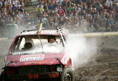 A little smoke and a missing tire was not enough to keep Joe Henry, from Woodstock from winning the SUV class of the Demotion Derby with his Dodge Caravan at the McHenry County Fair on Sunday, August 7, 2016 in Woodstock.  John Konstantaras photo for the Northwest Herald