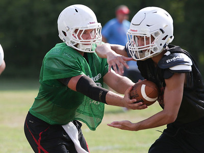 Gavin Scott hands off to Elias Edmondson during Marian Central football practice on Wednesday August 10, 2016 in Woodstock.  John Konstantaras photo for the Northwest Herald