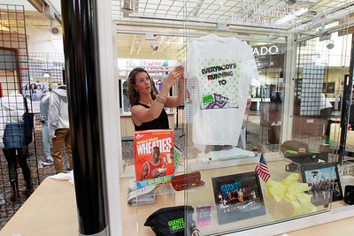 Candace H. Johnson Erin McGraw, publicist, hangs up an old t-shirt in the time capsule display at Entry E outside of Bass Pro Shops Outdoor World after it was discovered during the public unearthing of a 1991 time capsule to commemorate the 25th Anniversary of Gurnee Mills in Gurnee.