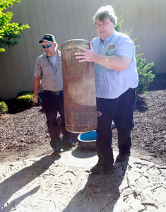 Candace H. Johnson Phil Dohm, maintenance, and Peter LeBlanc, operations supervisor, carry the time capsule buried outside of Entry B to a table to open it during the public unearthing of the 1991 time capsule to commemorate the 25th Anniversary of Gurnee Mills in Gurnee.