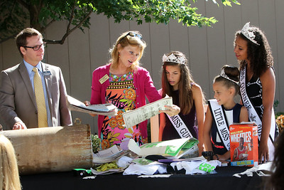 Candace H. Johnson Randy Ebertowski, general manager, watches as the Mayor of Gurnee, Kristina Kovarik, looks at old newspapers with the Gurnee 2016 Queens: Jr. Miss: Emily Hetman, 12, Little Miss: Morgan Ghys, 9, and Miss: Leah Davis, 17, discovered during the public unearthing of a 1991 time capsule to commemorate the 25th Anniversary of Gurnee Mills in Gurnee.