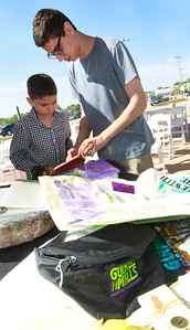 Candace H. Johnson Yousef Joseph, 9, of Pleasant Prairie, Wis., and his brother, Ashad, 17, look at a Gurnee Mills pen discovered along with several items during the public unearthing of a 1991 time capsule buried at Entry B to commemorate the 25th Anniversary of Gurnee Mills in Gurnee.