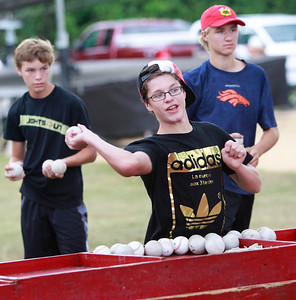 Candace H. Johnson Tommy Keilwitz, of Round Lake Beach, and Christian Swenson, of Lake Villa watch Bradley Gonyea, of Lake Villa, (center) all 13, hit the target attached to the Big Dipper dunk tank during Lake Villa Days at Lehmann Park in Lake Villa.