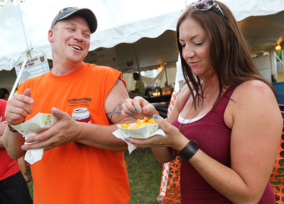 Candace H. Johnson James Lewis, of Ingleside shares a laugh with Suzi Aschenbrener, of Antioch while they eat cheese fries during Lake Villa Days at Lehmann Park in Lake Villa.