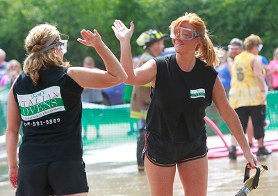 Candace H. Johnson Tina Rinkenberger, of Ingleside, high-fives Patty Clavey, of Lake Villa, both with the Ron's Italian Ovens team, after beating Results Realty in a water fight during Lake Villa Days at Lehmann Park in Lake Villa.