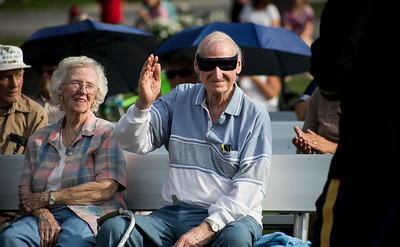 "Mike Greene - For Shaw Media  WWII Veteran Eugene Miller, right a 9th Air Force Corporal, raisees his hand to be recognized while sitting with his wife Clarice during McHenry's seventh annual event celebrating the end of World War II Sunday, August 14, 2016 at Veterans Memorial Park in McHenry. The annual event included swing music by  Bill's Little Big Band, Military Honor Guard Salute with ""Taps"" played by 18 Buglers as well as a 21 white dove release."
