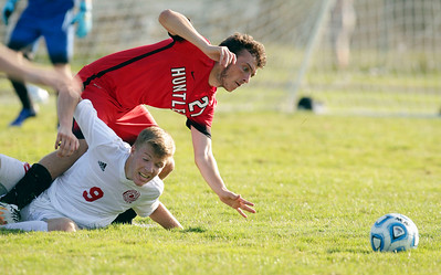 Andrew Meyer (21) of Huntley and Sam Guilbeault (9) of Marian Central Catholic fall over each other as they chase a ball during the second half of their game at Marian Central Catholic High School on Wednesday, August 24, 2016 in Woodstock, Ill. The Red Raiders defeated the Hurricanes 4-1.  John Konstantaras photo for the Northwest Herald