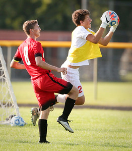 Drew Simmons (2) of Marian Central makes a save in front of Aaron Ruffner (8) of Huntley during the second half of their game at Marian Central Catholic High School on Wednesday, August 24, 2016 in Woodstock, Ill. The Red Raiders defeated the Hurricanes 4-1.  John Konstantaras photo for the Northwest Herald