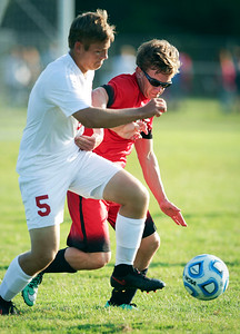 Ryan Janikowski (13) of Huntley  and Jacob Klaus (5) of Marian Central Catholic chase a ball during the second half of their game at Marian Central Catholic High School on Wednesday, August 24, 2016 in Woodstock, Ill. The Red Raiders defeated the Hurricanes 4-1.  John Konstantaras photo for the Northwest Herald