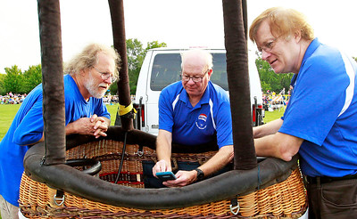 Candace H. Johnson Jim Neill, of Riverwoods, Pat Hall of Naperville and Bennett Schwontkowski, of Cary check the radar for bad weather during the Color Aloft Balloon Festival in Central Park in Grayslake. The balloons were not inflated due to weather conditions.