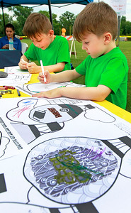 Candace H. Johnson Elliot Scharm, 6, of Lake Villa and his brother, Silas, 5, color balloon pictures during the Color Aloft Balloon Festival in Central Park in Grayslake. The Grayslake, Lake Villa and Round Lake libraries sponsored the coloring table.