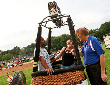Candace H. Johnson Andres Padilla and Maria Hoyos, both of Waukegan stand in the basket as they talk with Bennett Schwontkowski, a pilot for the Re/Max Northern Illinois balloon, about the burner during the Color Aloft Balloon Festival in Central Park in Grayslake. The balloons were not inflated due to bad weather.