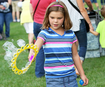 Candace H. Johnson Stella Lenox, 7, of Volo plays with a bubble wand during the Color Aloft Balloon Festival in Central Park in Grayslake.