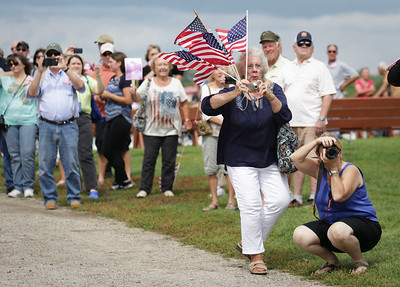 Lynnea Semasko, left, and Sue Thompson, both from Arlington Heights, take pictures as veterans arrive at the Veterans of Valor picnic at Stade Farm Market on Saturday, August 27, 2016 in McHenry. The event welcomes home and honors WWll, Korean, and Vietnam veterans arriving back from an Honor Flight to Washington DC with a warrior watch riders escort. Semasko and Thompson were there to meet Thompson's father Robert Schmid, who served in the Air Force during World War II.  John Konstantaras photo for the Northwest Herald