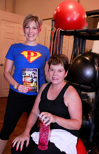 "Candace H. Johnson Nancy Hildebrandt, director, holds her book, ""Stronger Than Ever,"" with one of her clients, Jane Collins, of Libertyville at  Pinnacle Fitness in Libertyville. Collins is featured working out on the cover of Nancy Hildebrandt's book."