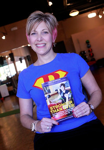 "Candace H. Johnson Nancy Hildebrandt, holds her book, ""Stronger Than Ever,"" at Pinnacle Fitness in Libertyville."