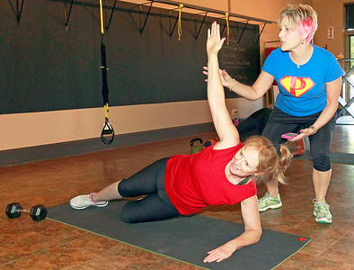 Candace H. Johnson Nancy Hildebrandt, director, works with her client, Rachel Reich, of Grayslake, on a side plank during a small group training session at Pinnacle Fitness in Libertyville.