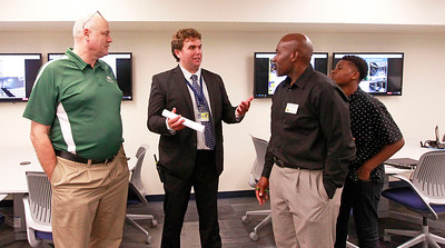 Candace H. Johnson Mike Baird, division chairman of math and business, (second from the left) talks with Hal Davis, of Round Lake Beach, David Northern, Sr., of Round Lake and his son, David Northern, Jr., 12, in the Incubator classroom where business and entreprenuer classes are held after the ribbon cutting ceremony at Round Lake High School. Baird told the story of how drips of water used to fall on him from the ceiling while he taught in the old business classroom.
