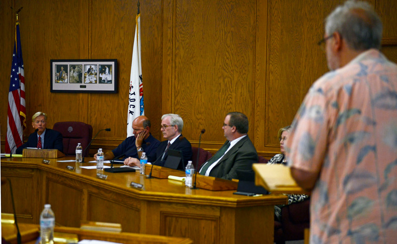 Woodstock Mayor Dr. Brian Sager, far left,  speaks with a Woodstock resident about potential other sources of revenue such as parking meters in the square to make money rather than an increase in sales tax during a city council meeting Tuesday, Aug. 1, 2017 at the City Hall in Woodstock. There was a public hearing held for community members to comment on a proposed sales tax increase.