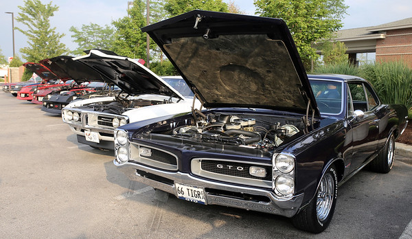 Classic cars are lined up with hoods open at McDonalds in Sugar Grove on July 20 during the Rock & Roll Roadshow.
