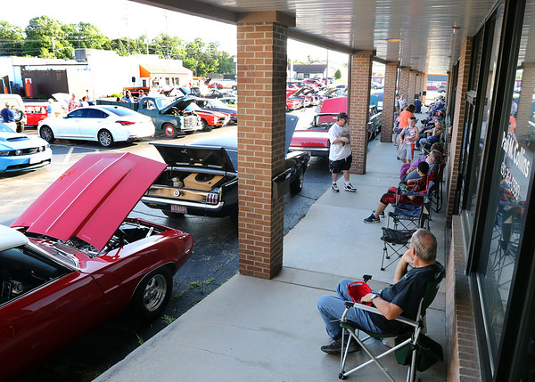 Car owners rest in the shade during a Rock & Roll Roadshow cruise night at the A&W in North Aurora July 1.