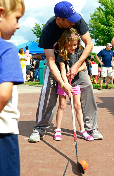 Kayla Wolf - for Shaw Media Jonathan Feinstein helps his daughter Kenzie Feinstein swing a hockey stick as his son Jack Feinstein, far left, watches during Blast on the Beach on Saturday, Aug. 5, 2017, at Main Beach in Crystal Lake. The event was sponsored by the Crystal Lake Park District and Crystal Lake Chrysler Jeep Dodge Ram.