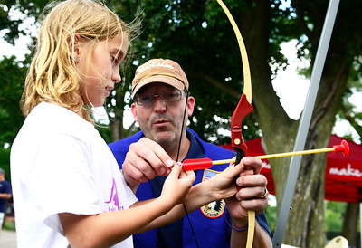 Kayla Wolf - for Shaw Media Olivia Flaig(cq) is assisted by Tom Gau (cq) in stringing an arrow at a booth sponsored by the Indian Guides and Princesses of McHenry County on Saturday, Aug. 5, 2017 during the Blast on the Beach at Main Beach in Crystal Lake. The event was sponsored by the Crystal Lake Park District and Crystal Lake Chrysler Jeep Dodge Ram.