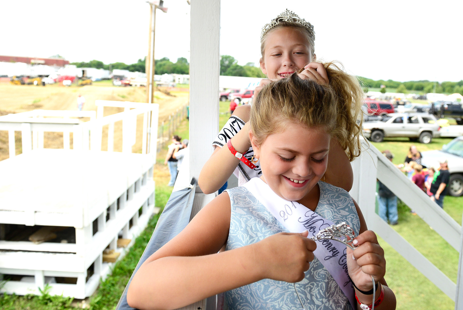 Kayla Wolf - for Shaw Media Prior to the demolition derby at the McHenry County Fair Junior Miss McHenry County Isabella Novalinski does the hair of McHenry County Princess Dominique Tomasello Sunday, Aug. 6, 2017, in Woodstock. The fair pageant winners welcomed the crowd to their derby and watched the events of the day.