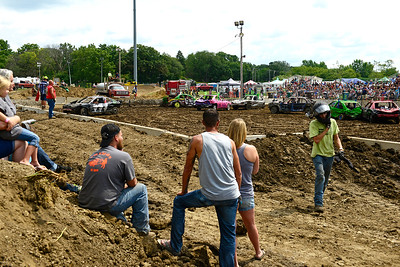 Kayla Wolf - for Shaw Media Cliff Fandrich, far right, walks away from his demolition derby car Sunday, Aug. 6, 2017, at the McHenry County Fair in Woodstock.