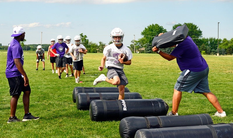 Kayla Wolf - for Shaw Media Hampshire senior Nic Rummell runs through a drill Monday, Aug. 7, 2017, as Coach Aaron Essex, left and Head Coach Michael Brasile, right try to knock the ball out of his arm. Monday was the first official day of practice at Hampshire High School.