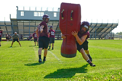 Kayla Wolf - for Shaw Media Marengo's Blake Heinberg, left releases a tackling dummy to a teammate during practice Tuesday, Aug. 8, 2017, at Marengo High School.