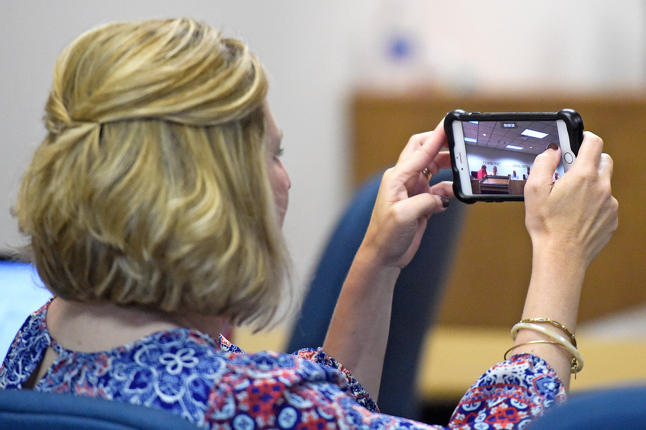 Kayla Wolf - for Shaw Media Director of Student Services Kimberly Dahlem takes a video of the District 155 Board of Education voting on appointing Steve Olson interim superintendent  of the district Wednesday, Aug. 9, 2017 at the Center for Education in Crystal Lake. Board members said prior to their executive session that the resignation of former superintendent  Johnnie Thomas was unexpected.