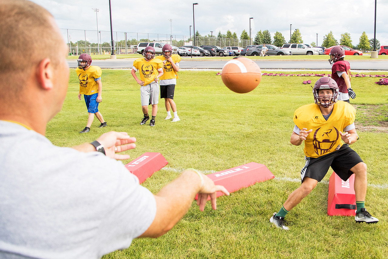 Richmond Burton High School Co-Head Coach Tad DePorter (left) runs a drill with James Horner (right) during football practice Friday, August 11, 2017 in Richmond. KKoontz- For Shaw Media