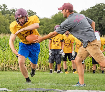 Richmond Burton High School's Mike Kaufman (left) takes a hand-off from Co-Head Coach Brett Zick during football practice Friday, August 11, 2017 in Richmond. KKoontz- For Shaw Media