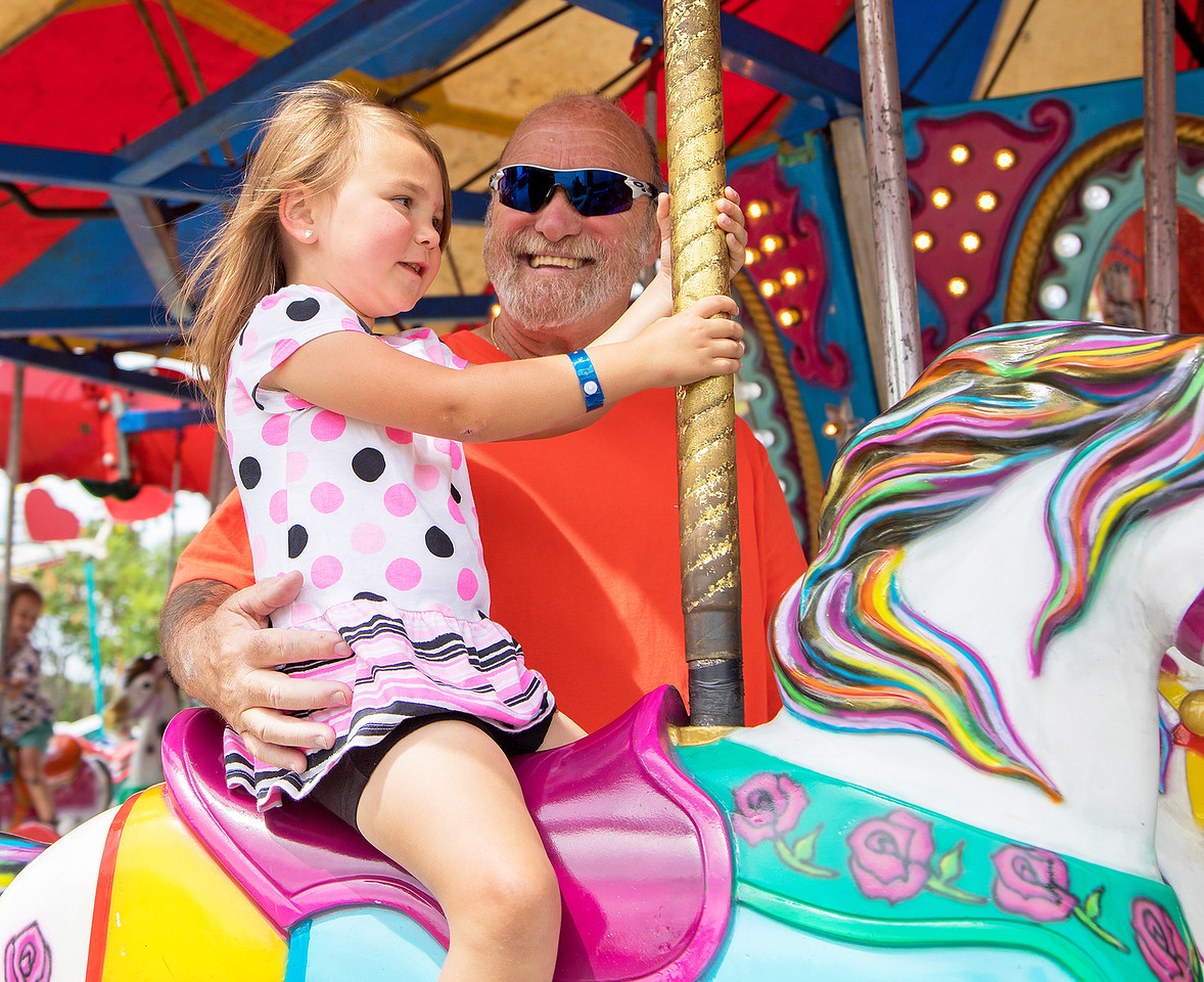 Don Malachuk and granddaughter Dani take a spin on the merry-go-round during the annual Lakemoor Fest Sunday, August 13, 2017 in Lakemoor. KKoontz – for Shaw Media