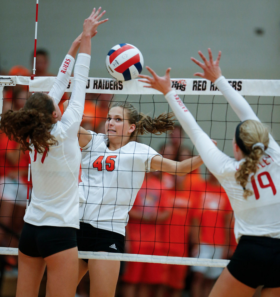 Madeline Timmerman (45) from Crystal Lake Central scores a post past Emma Konie (17) and Loren Alberts (19) from Huntley during their first game at Huntley High School on Tuesday, August 22, 2017 in Huntley. The Red Raiders defeated the Tigers in 3 games; 28-26, 18-25, 25-12John Konstantaras photo for the Northwest Herald