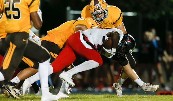 Dominic Barone (27) from Huntley is tackled by Jermaine Maegdlin-Ferguson (1) from Jacobs after running for a first down during the fourth quarter of their game at Jacobs High School on Friday, August 25, 2017 in Algonquin, Illinois. The Red Raiders defeated the Golden Eagles 30-27. John Konstantaras photo for the Shaw Media