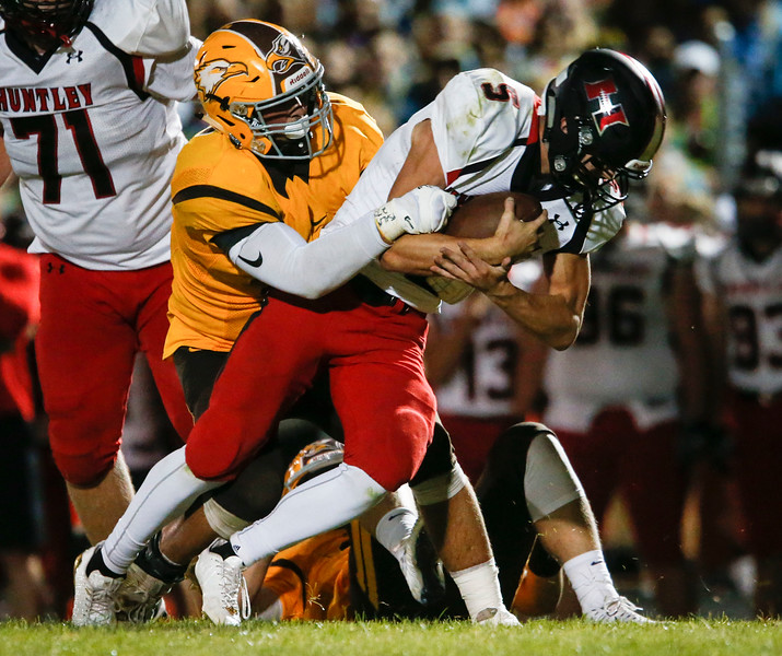 Eric Mooney (5) is tackled by Tyson Pachniak (46) from Jacobs during the fourth quarter of their game at Jacobs High School on Friday, August 25, 2017 in Algonquin, Illinois. The Red Raiders defeated the Golden Eagles 30-27. John Konstantaras photo for the Shaw Media