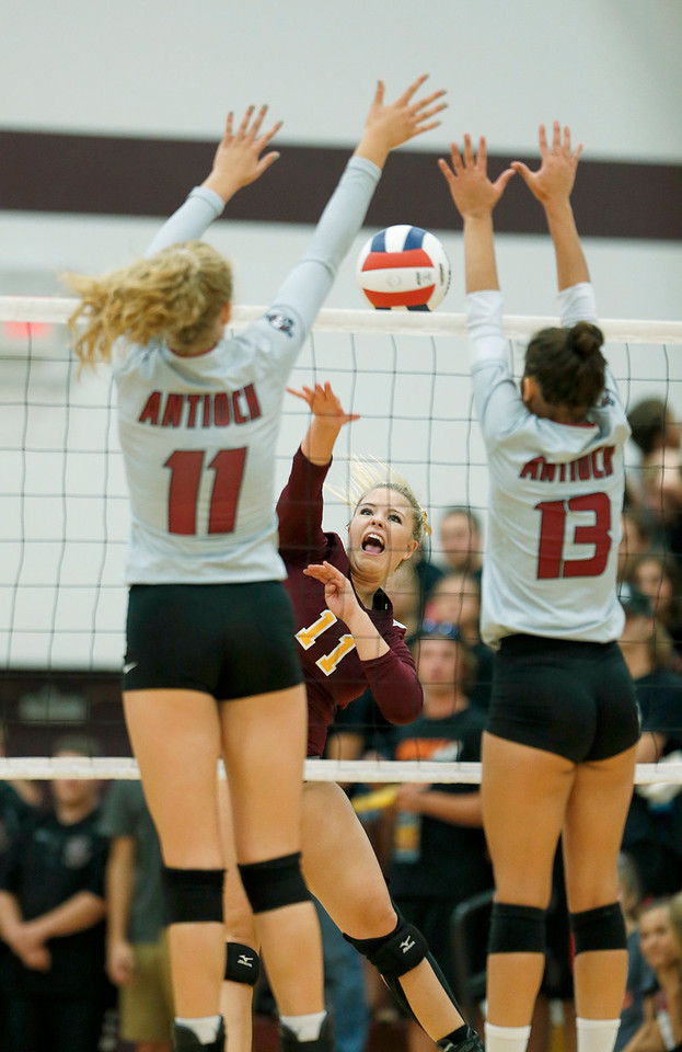 John Konstantaras - for Shaw Media Richmond-Burton's Sarina Keim (11)  hits the ball as Antioch's Kat Barr (11) and Cenie Frieson (13) defend at the net during their first game on Monday, August 28, 2017 in Richmond. The Sequoits defeated the Rockets in 2 games; 15-25, 23-25.