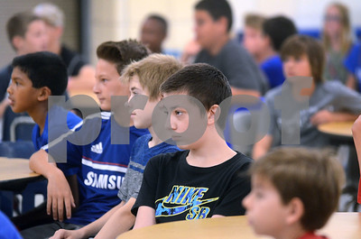 Students who will be starting their first year at Herrick Middle School listen intently to instructions Aug. 14 during a sneak preview day for incoming seventh-graders at the school in Downers Grove. Mark Busch - mbusch@shawmedia.com