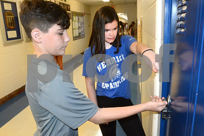 Donovan Barry gets some help opening a locker from eigth-grade helper Maeve Dietrich Aug. 14 during a sneak preview day for incoming seventh-graders at Herrick Middle School in Downers Grove. Mark Busch - mbusch@shawmedia.com