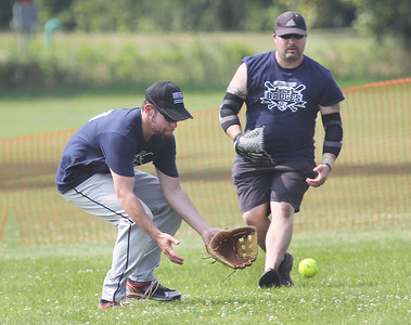 "Candace H. Johnson-For Shaw Media Gurnee Police's Mike Lambert fields a ground ball with J.R. Nauseda as backup against Gurnee Fire during the Gurnee Days ""Battle of the Badges"" softball game at Viking Park in Gurnee. (8/12/18)"